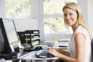 Woman in home office with computer smiling