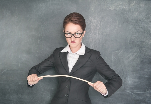 Angry teacher in glasses with wooden stick